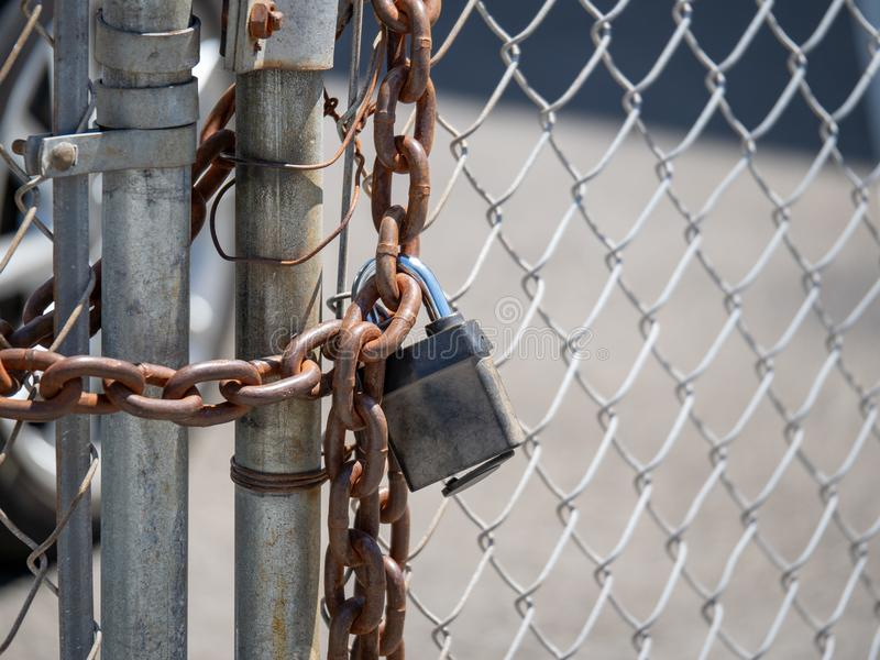 Sturdy chain wraps a chain link fence, closed with a padlock royalty free stock image