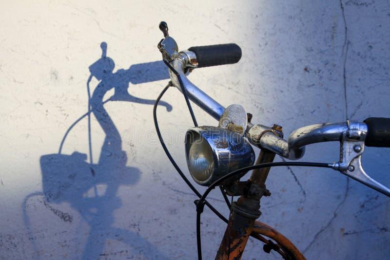 Sturen van oude roestige fiets die schaduwen op witte muur werpen royalty-vrije stock foto's