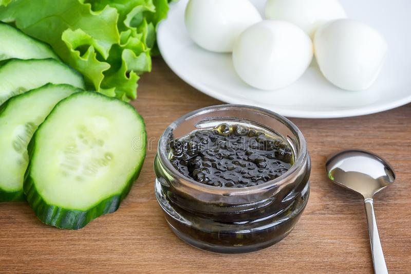 Sturgeon black caviar in small glass jar, few boiled quail eggs, some slices of cucunmber and fresh green lettuce on a brown stock photography