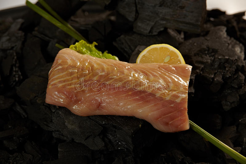 Sturgeon fillet. A sturgeon fillet on coals ready for cooking with some herbs and a pies of lemon royalty free stock images