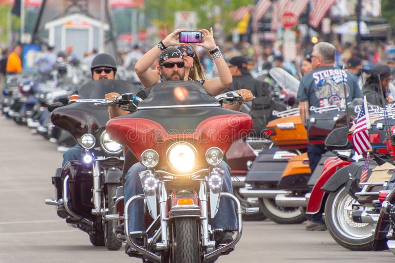 Sturgis, South Dakota motorcycle rally. AUGUST 5, 2018, STURGIS, SD: This biker practices safe documentation of the ride down Main Street at the annual Sturgis stock photography