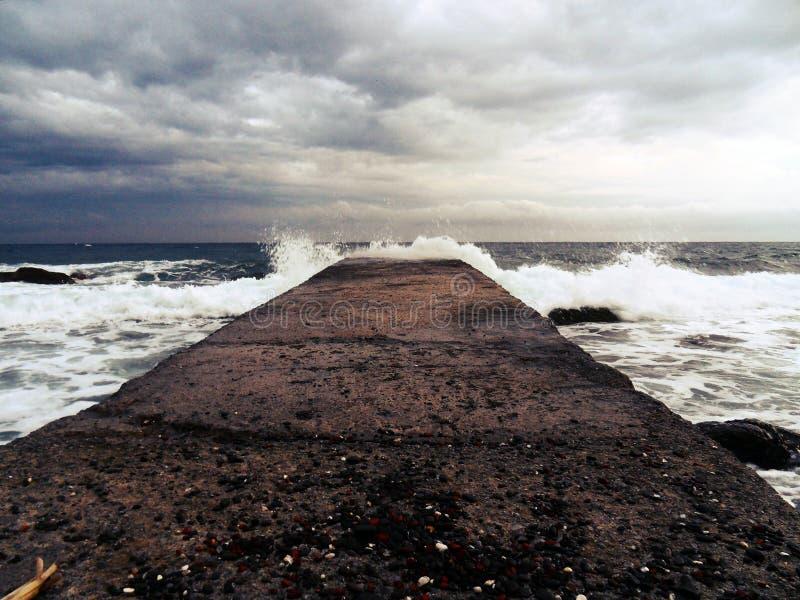 Sturla vågorna bryter på pir royaltyfri fotografi