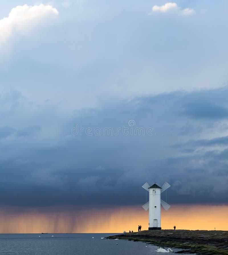 Sturm, der über den Leuchtturm bei Sonnenuntergang überschreitet lizenzfreie stockfotografie