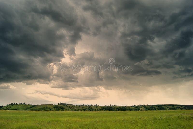 Sturmwirbelsturm über Sommerfeldern, -hügeln und -wäldern stockfotografie