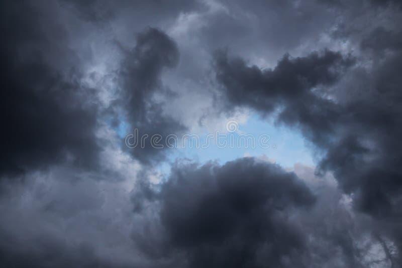 Sturmwolken im Hintergrund des blauen Himmels Dunkelheit und Licht Gut und Böse Ein Stück des blauen Himmels stockbild