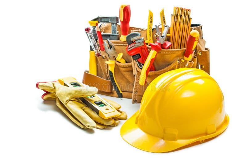 Sturzhelmhandschuhe und Bauwerkzeuge im Werkzeuggurt lokalisiert auf Weiß lizenzfreies stockbild