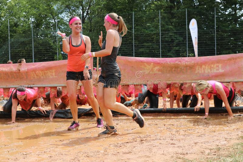 Stuttgart, Germany - July 21, 2019: Muddy Angels Run. Two team mates give a High-Five after completing a muddy obstacle at the Muddy Angel 5k Mud Run in royalty free stock photo