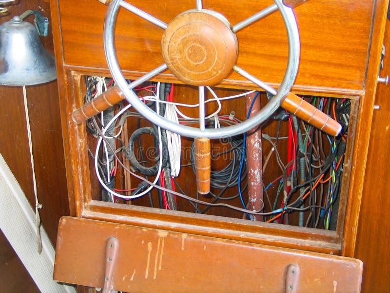 Stuurwiel en blootgesteld bedradings binnenroer van oude houten boot royalty-vrije stock fotografie