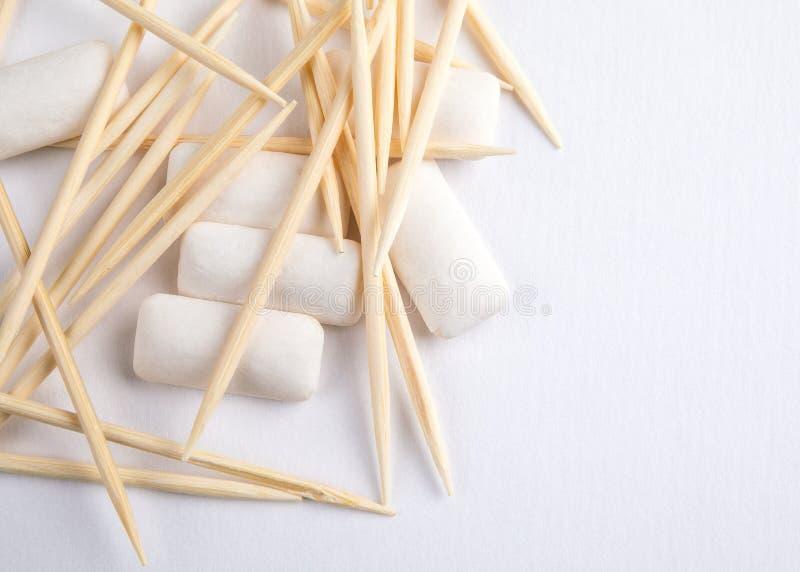 Stuzzicadenti e gomma da masticare su fondo bianco fotografia stock libera da diritti