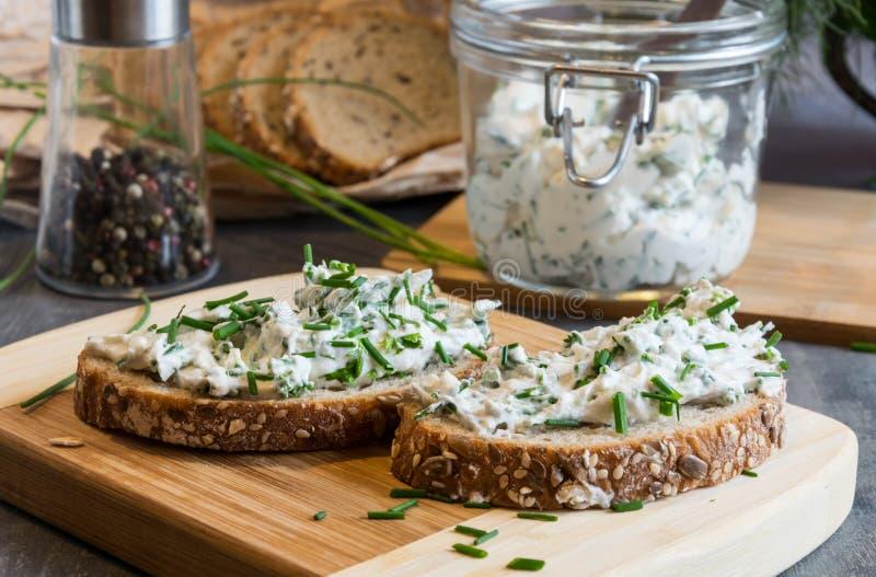 Stwarza ognisko domowe robić chleb na drewnianej tnącej desce z curd serem, ricotta i ziele Dekorujący z zielonymi ziele zdjęcie stock