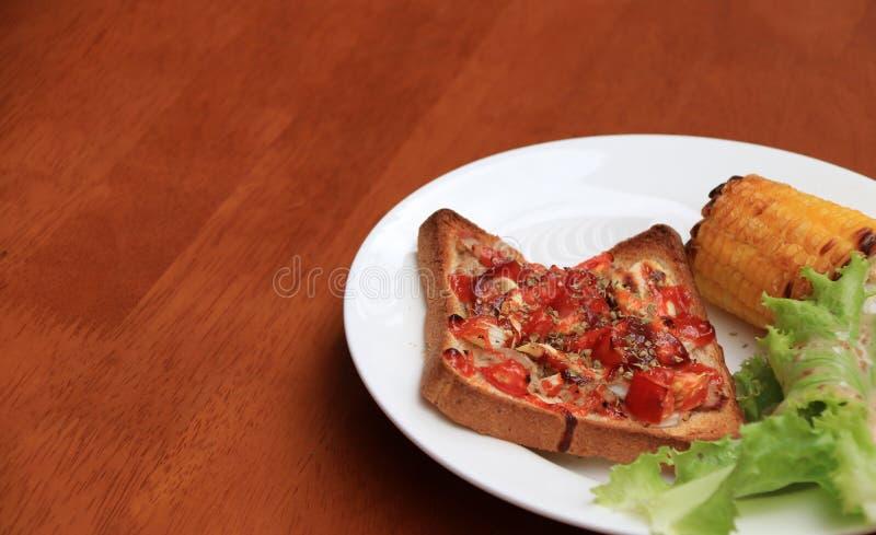 Stwarza ognisko domowe robić pizzę na kwadratowym pokrojonym chlebie z piec na grillu sałatą w białym round talerzu na drewnianym zdjęcia royalty free