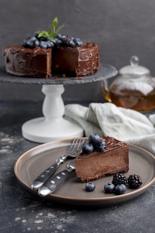 Stycke av chokladkakan med den hela kakan bakom på grå bakgrund arkivfoto