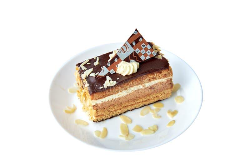 Stycke av chokladkakan med mandeln och choklad på vit isolerat Rund platta med mandeln close upp royaltyfria bilder