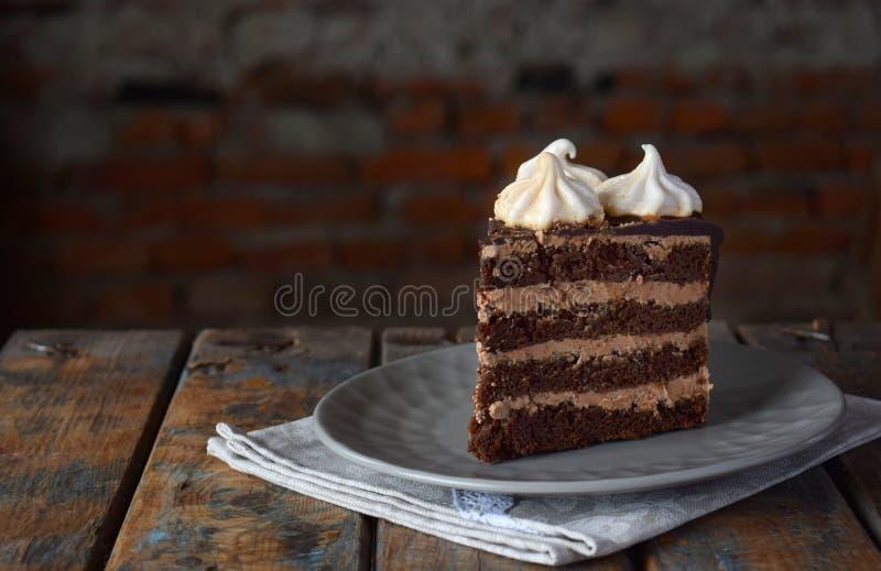 Stycke av chokladkakan som dekoreras med rosetter av mar?ngkr?m: choklad-mutter kex, karamellkr?m stekhett hemlagat royaltyfri bild