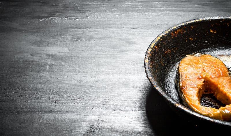 Stycke av den grillade laxen i en gammal panna fotografering för bildbyråer