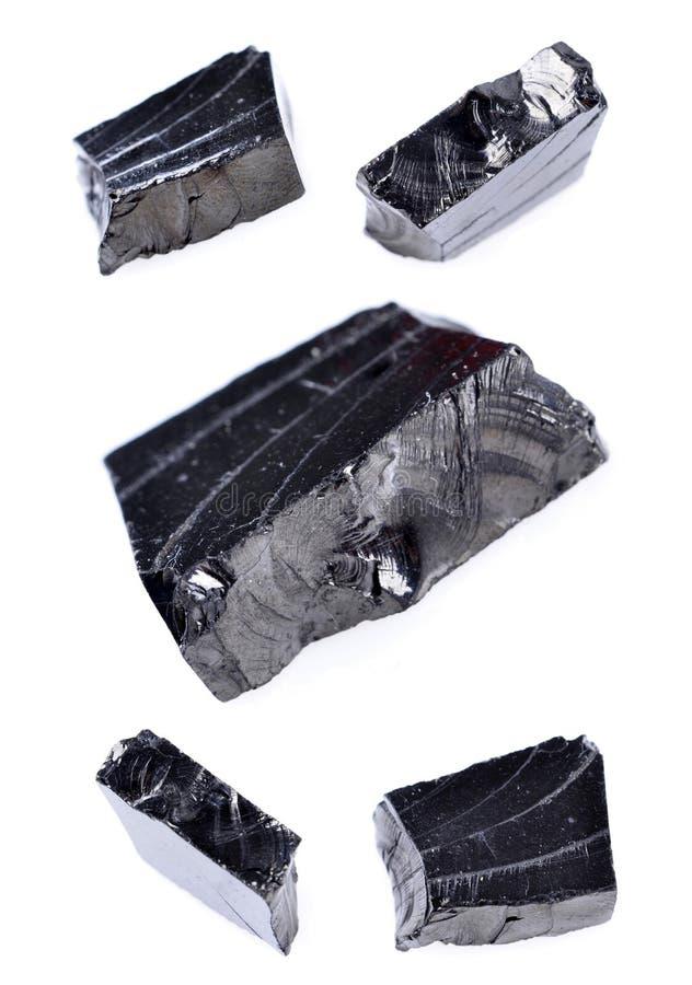 Stycke av den rå shungitegemstonen, svart Obsidian fotografering för bildbyråer