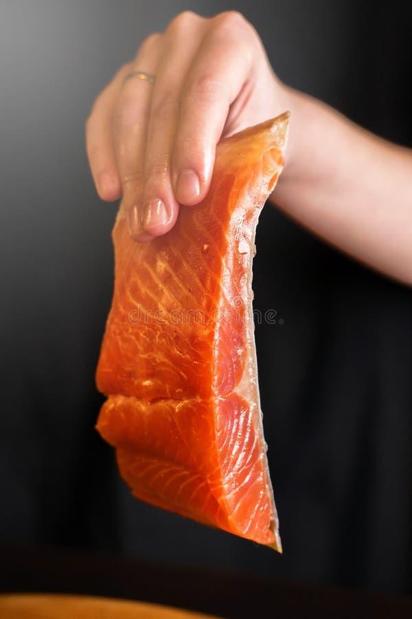Stycke av den röda fisken i hand royaltyfri bild