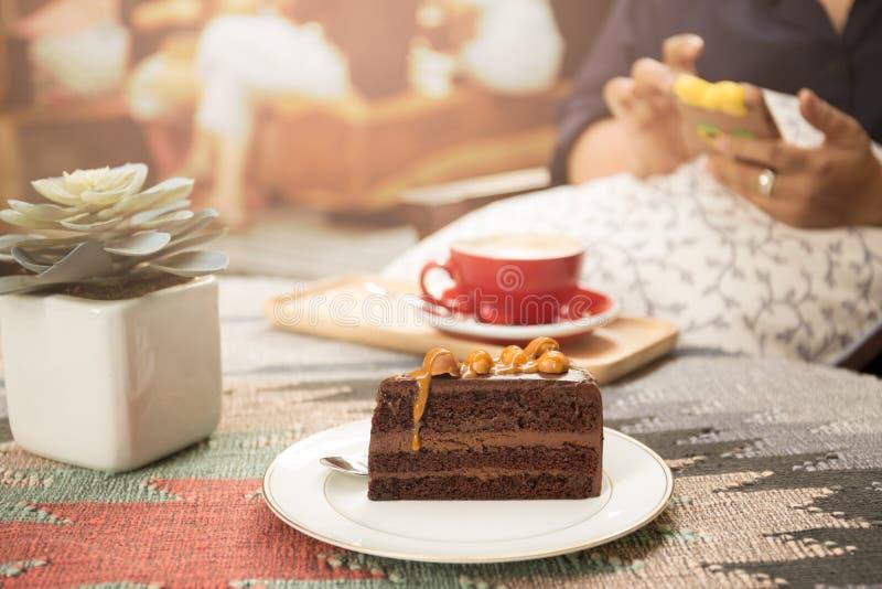 Stycke av den söta macadamiachokladkakan med koppen kaffe och s royaltyfria bilder