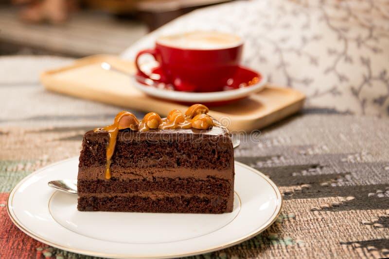 Stycke av den söta macadamiachokladkakan med den röda koppen kaffe royaltyfria foton