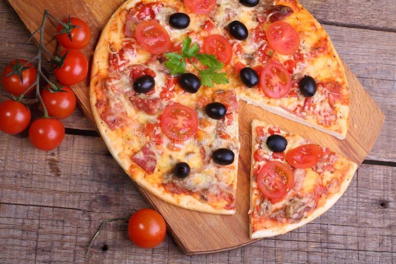 Stycke av en pizza och pizza från en salami, en skinka och tomater på royaltyfri bild