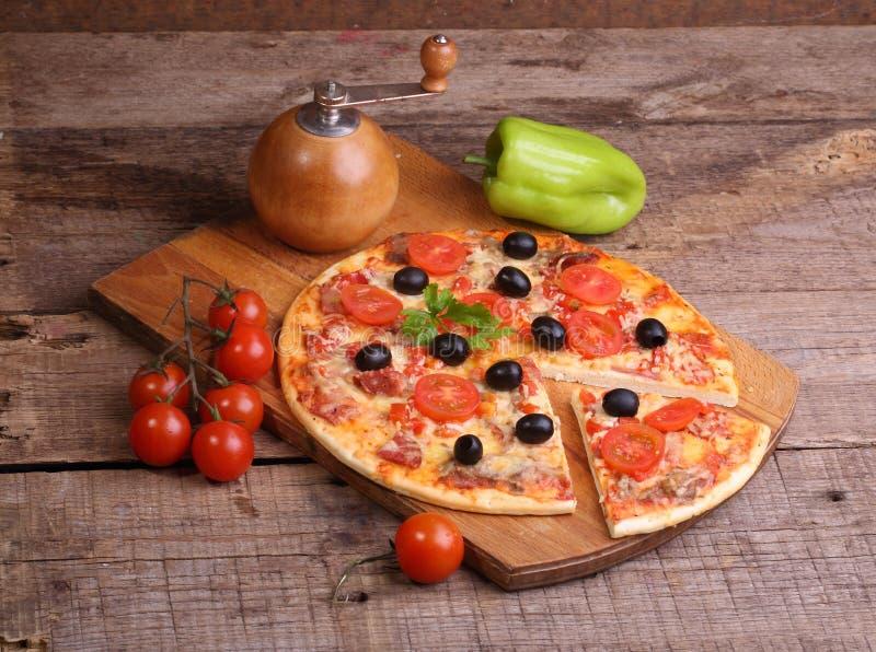 Stycke av en pizza och pizza från en salami, en skinka och tomater på arkivfoto