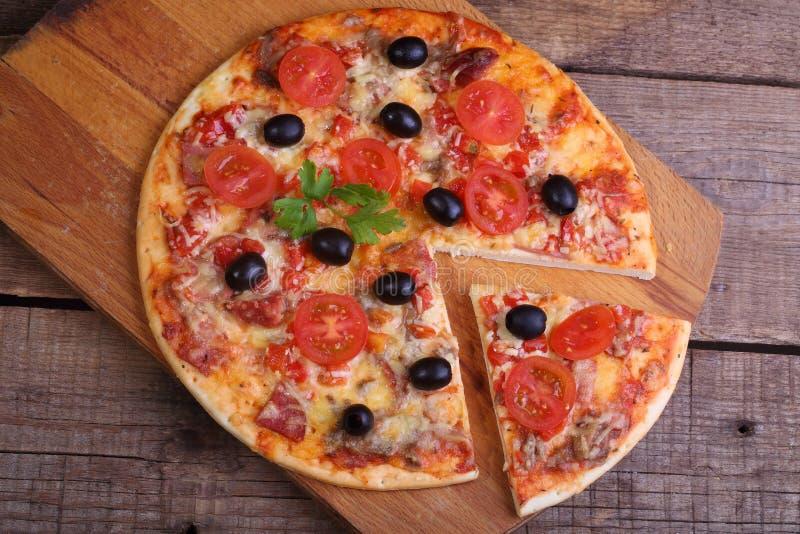 Stycke av en pizza och pizza från en salami, en skinka och tomater på royaltyfri foto