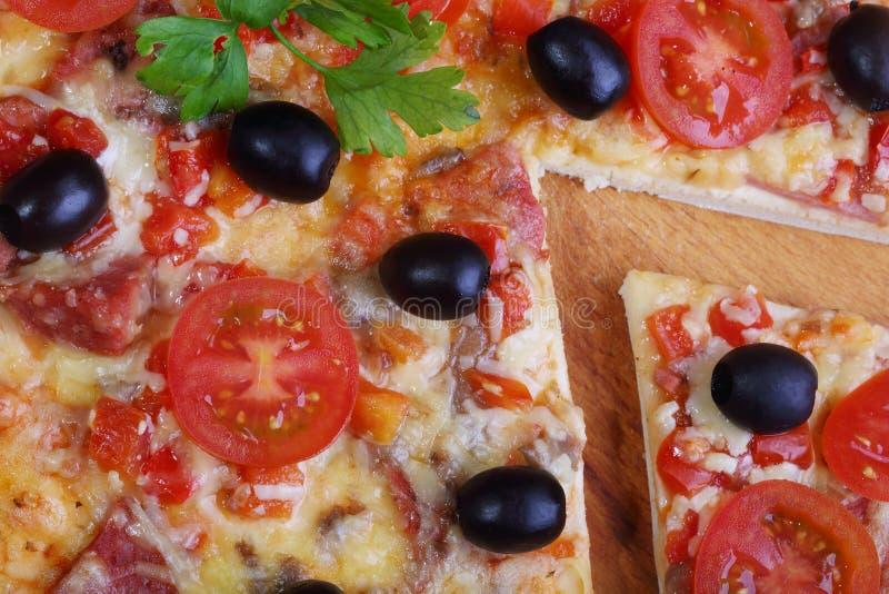 Stycke av en pizza och pizza från en salami, en skinka och tomater på fotografering för bildbyråer