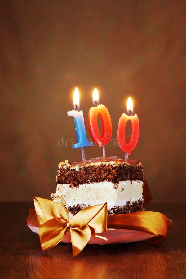 Stycke av födelsedagkakan med bränningstearinljuset som nummer hundra royaltyfri fotografi