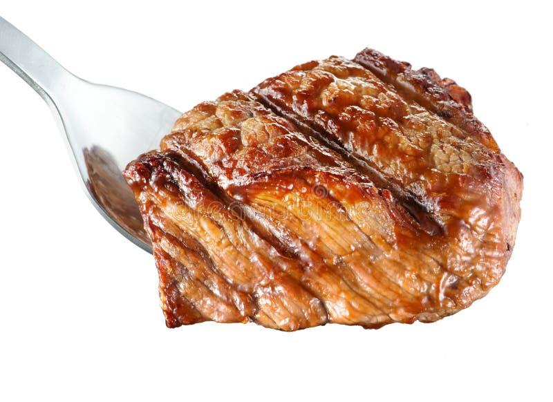 Stycke av grillat kött. Stöd-öga biff på gaffel. Vit bakgrund fotografering för bildbyråer