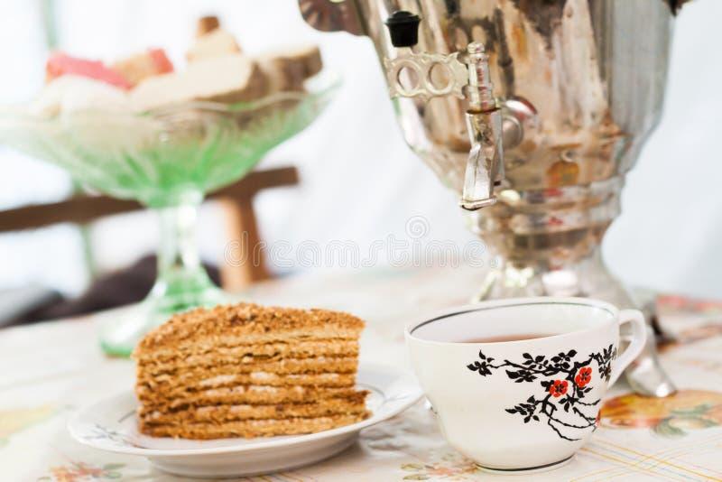 Stycke av kakahonungkakan på en platta, en kopp te och en samovar fotografering för bildbyråer