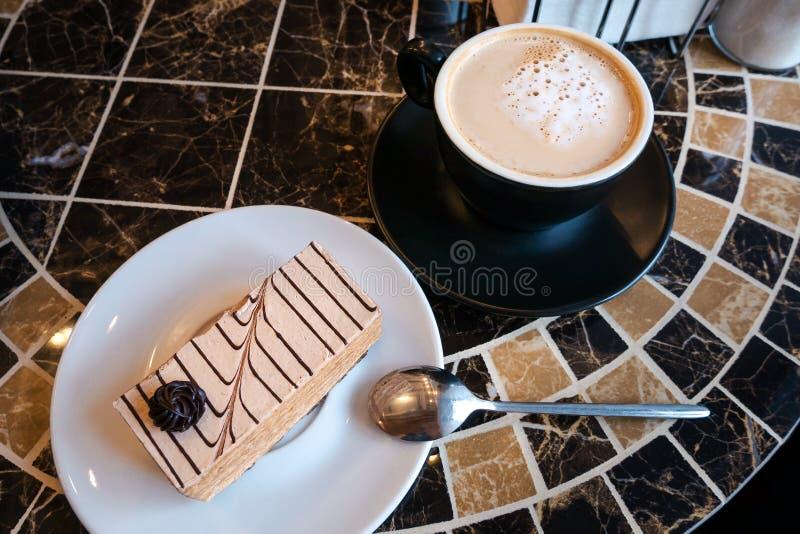 Stycke av kakan på den vitt plattan och cappuccinokaffe i svart kopp och tefat arkivfoto