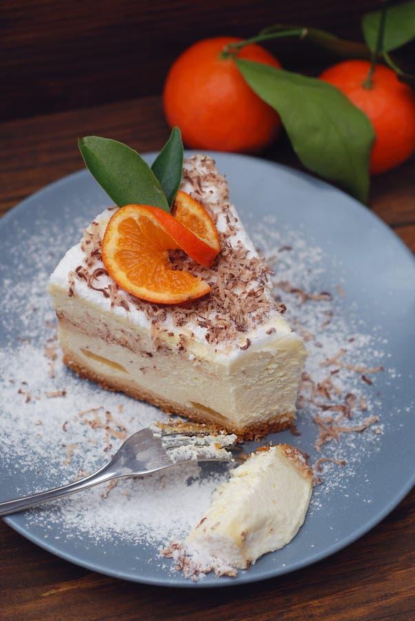 Stycke av läcker hemlagad vit ostkaka med tangerin på Gray Plate med Sugar Powder Mörkt trälantligt royaltyfria foton