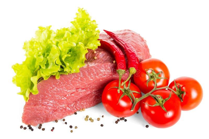 Stycke av nya kalvkött, grönsallatsidor, tomater och peppar som isoleras på vit arkivfoto