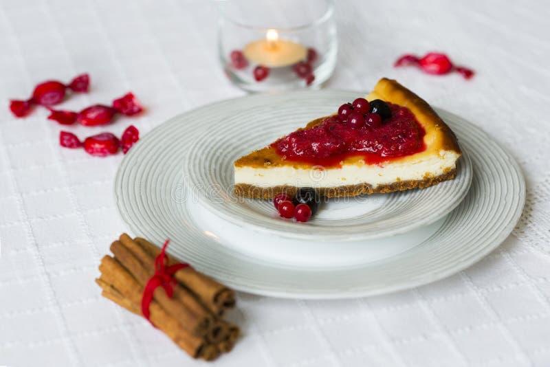 Stycke av ostkaka med röda och svarta bär överst av det på den vita plattan med kanelbruna pinnar med den röda rad- och brännings fotografering för bildbyråer