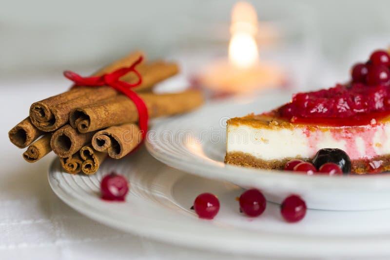 Stycke av ostkaka med röda och svarta bär överst av det på den vita plattan med kanelbruna pinnar med den röda rad- och brännings arkivbilder