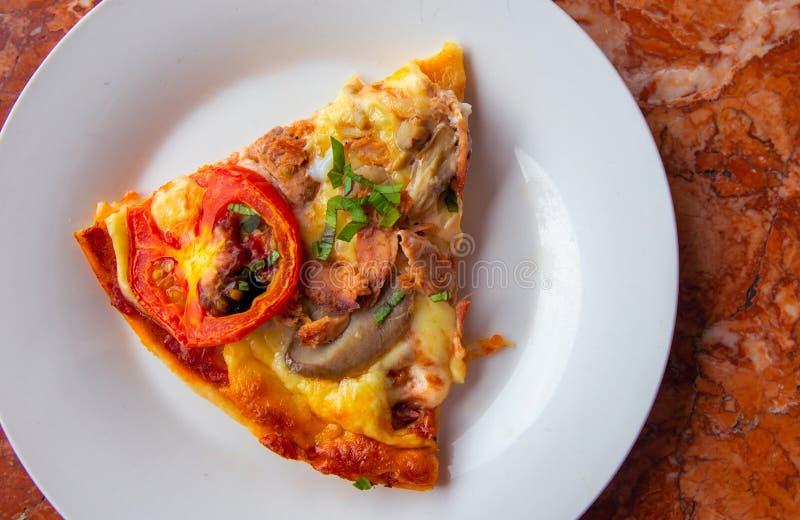 Stycke av pizza med tomaten, örter och ost på den vita plattan Pizzaskiva på bästa sikt för stentabell Smaskig ny pizza arkivfoto