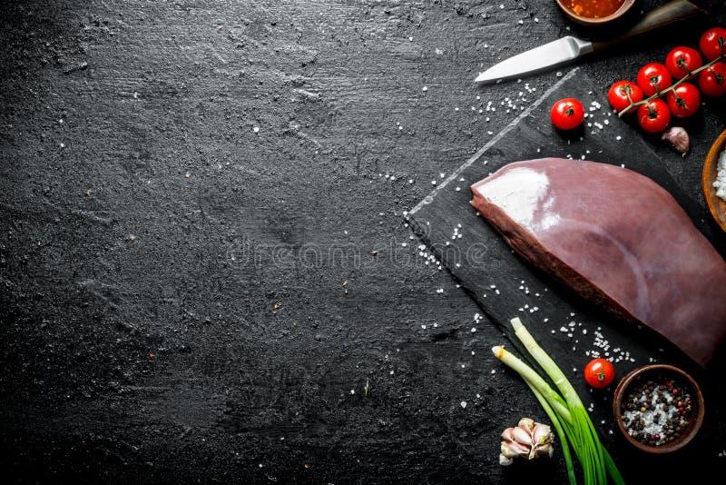 Stycke av rå lever med salladslökar, vitlök och tomater arkivbilder