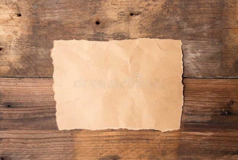 Stycke av sönderrivet papper på gammalt grungeträ royaltyfri bild