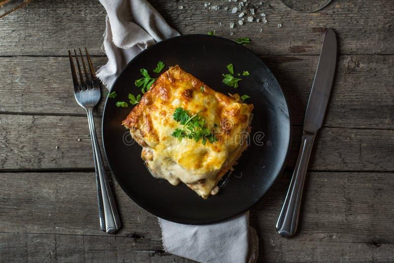 Stycke av smakliga varma lasagner med rött vin Litet djup av sätter in traditionell italiensk lasagna del italienska matlagningma royaltyfri bild