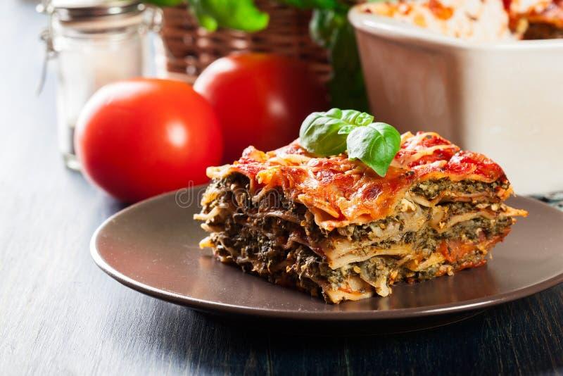 Stycke av smakliga varma lasagner med spenat på en platta royaltyfria bilder
