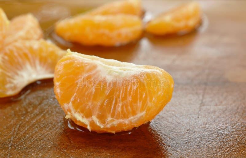 Stycke av tangerinapelsinen på träkotlettkvarteret arkivbild