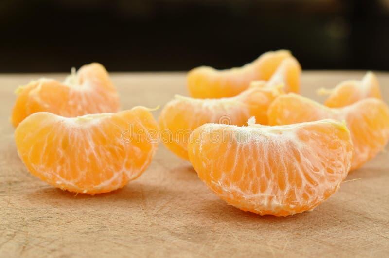 Stycke av tangerinapelsinen på träkotlettkvarteret royaltyfri foto