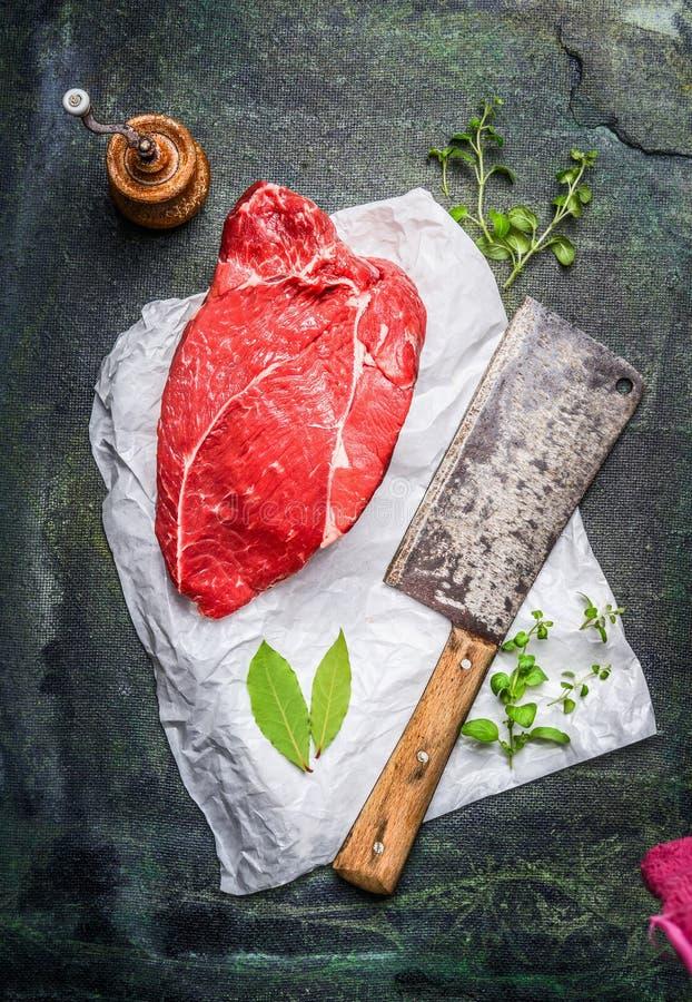 Stycke av utmärkt rått kött på vitbok med slaktareköttyxan, örter och kryddor royaltyfri foto
