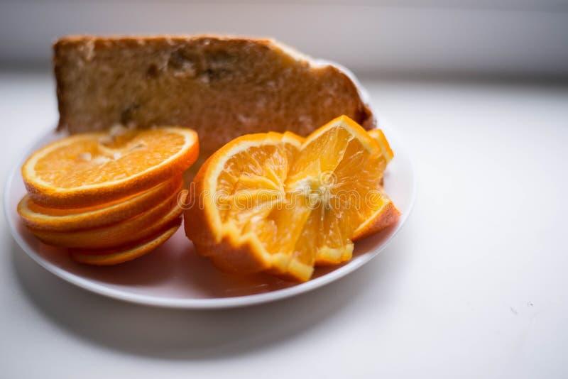 Stycken av apelsinen på en platta bredvid ett stycke av kakan fotografering för bildbyråer
