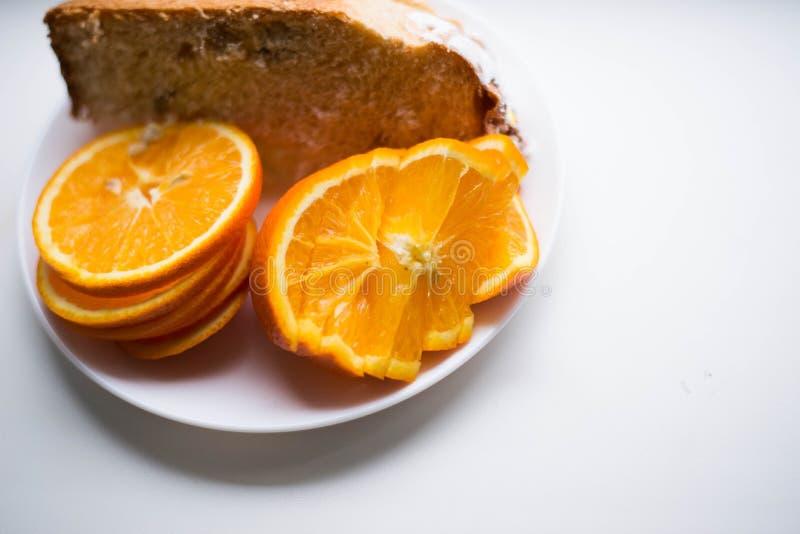 Stycken av apelsinen på en platta bredvid ett stycke av kakan arkivfoton