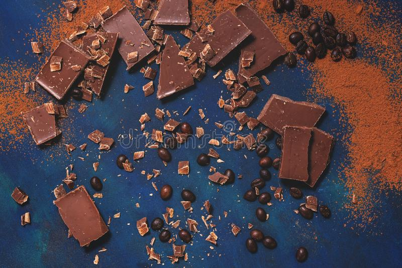 Stycken av choklad, grillade kaffebönor och kakaopulver på en blå bakgrund Bästa sikt, lekmanna- lägenhet arkivbilder