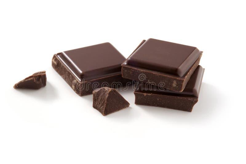 Stycken av choklad på vit arkivbild