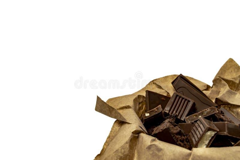 Stycken av choklader i ett tillverka papper p? en vit bakgrundscloseup royaltyfri fotografi