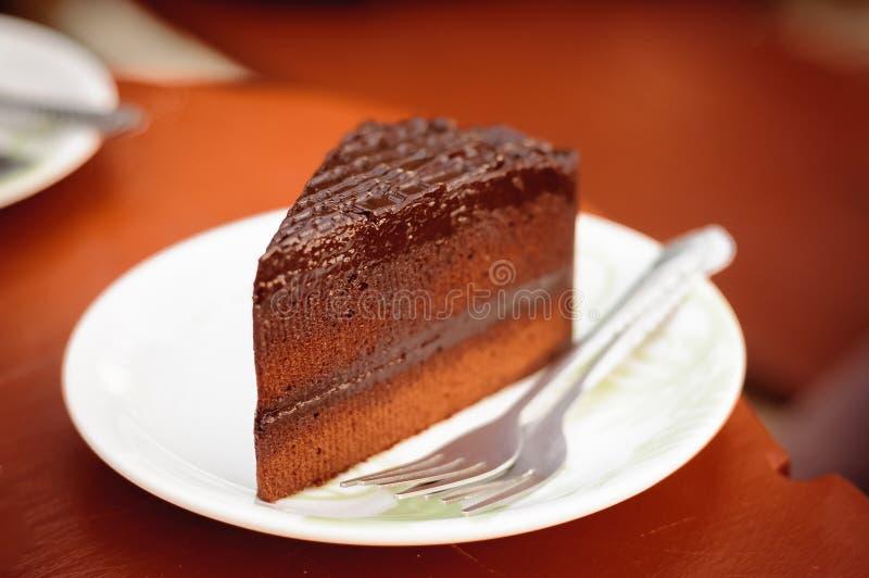 Stycken av den läckra chokladkakan med gaffeln på maträtt i kaffe s royaltyfri fotografi