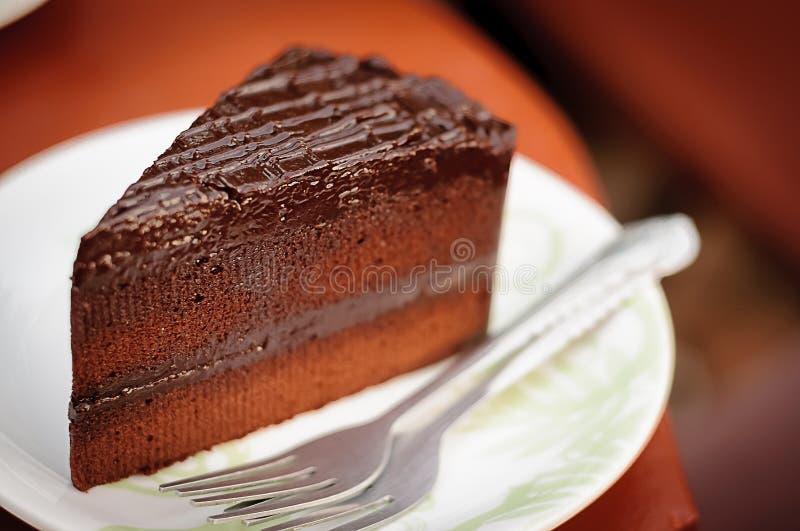Stycken av den läckra chokladkakan med gaffeln på maträtt i kaffe s arkivbilder